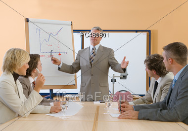 Business People Sitting at Conference Desk Stock Photo