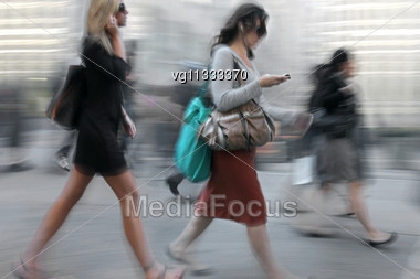 Business People Walking On The Street In Intentional Motion Blur, Both Women Using Mobile Phones, People In The Background Stock Photo