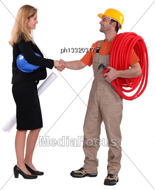 Business Professional Shaking A Tradesman's Hand Stock Photo