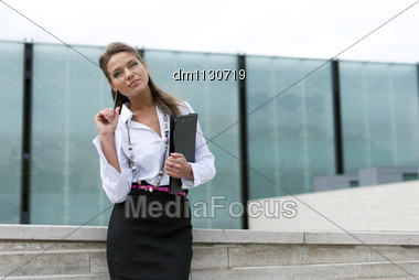 Business Woman In Black Skirt And Is Holding A Folder On The Business Background Of The Building Stock Photo