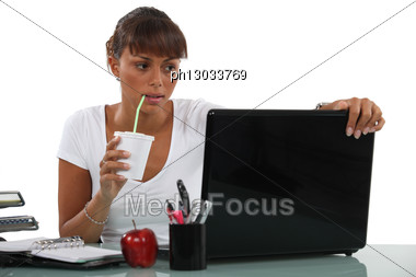 Business Woman Drinking At Desk Stock Photo