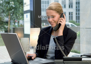 Business Woman On Telephone & Working On Laptop Stock Photo