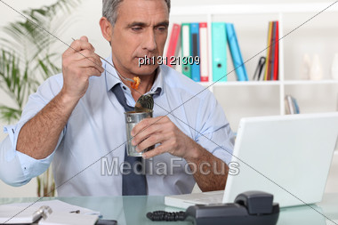 Businessman Eating Food From A Tin Stock Photo