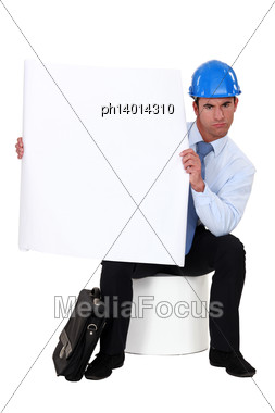 Businessman With A Helmet On His Head Holding A Blank Poster Stock Photo