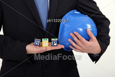 Businessman Holding A Hard Hat And Letter Blocks Stock Photo
