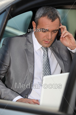Businessman In Car Talking On Phone Stock Photo