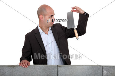 Businessman Looking At A Trowel. Stock Photo