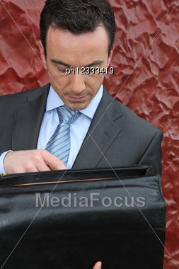 Businessman Looking In His Briefcase Stock Photo