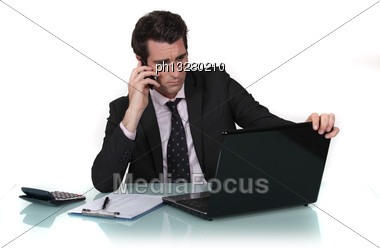 Businessman Making Call Whilst Reading From Computer Screen Stock Photo