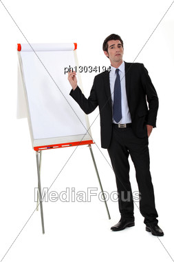 Businessman Pointing To A Flip Chart Stock Photo