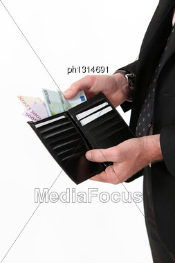 Businessman Pulling Out A Wad Of Money From His Wallet Stock Photo