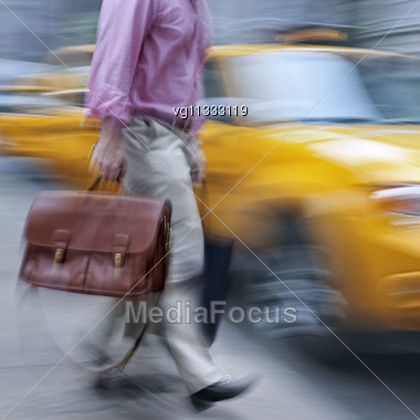 Businessman Rushing On The Street In Motion Blur Holding Red Leather Briefcase, Yellow Taxi Cab At Background Stock Photo