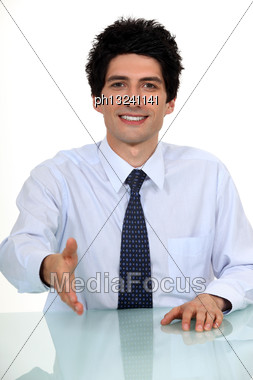 Businessman Sat At Desk Offering To Shake-hand Stock Photo