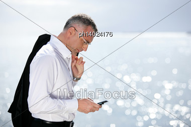 Businessman Sending A Text Message By The Seaside Stock Photo