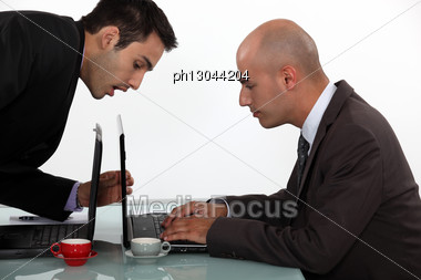 Businessman Sneaking A Peak At His Colleague's Work Stock Photo