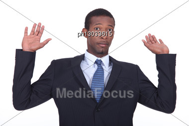 Businessman In A Suit Holding His Hands In The Air Stock Photo