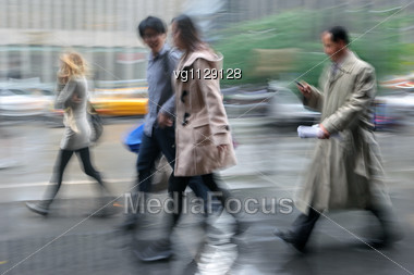 Businessman Walking On The Rainy Street In Intentional Motion Blur, Man Using Cell Phone, People Walking By Stock Photo