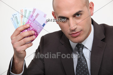 Businessman Waving A Wad Of Euros Stock Photo