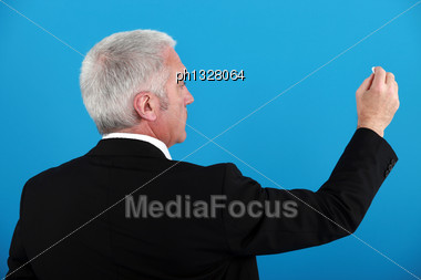 Businessman Writing On An Invisible Board Stock Photo