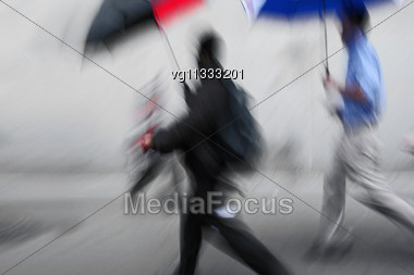Businessmen Rushing On The Rainy Street In Intentional Motion Blur Stock Photo