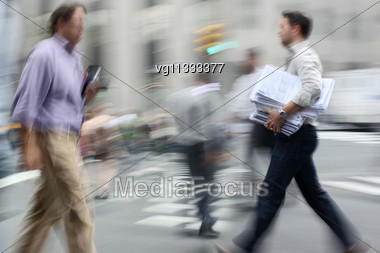 Businessmen Walking On The Street In Intentional Motion Blur Carrying Folder With Documents Stock Photo