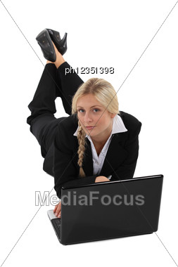 Businesswoman Lying On The Floor With Her Laptop Stock Photo