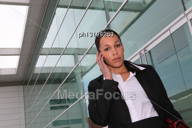 Businesswoman Making Phone Call Outside Office Stock Photo