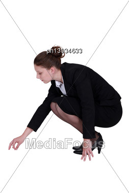 Businesswoman Picking A Speck Up Off The Floor Stock Photo