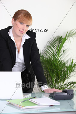 Businesswoman Standing At Her Desk Stock Photo