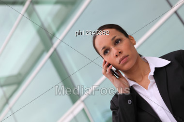 Businesswoman Using A Cellphone Outside An Office Block Stock Photo