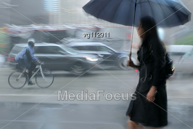 Businesswoman Walking On The Rainy Street In Intentional Motion Blur, Traffic In The Background Stock Photo