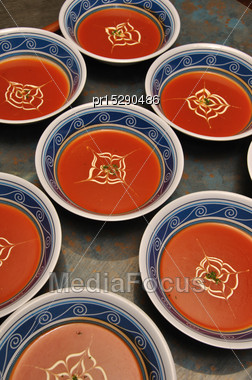 Busy Cooks Garnish Bowls Of Tomato Soup With Fresh Cream Stock Photo