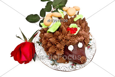 Cake In The Form Of A Hedgehog, Adorned With Green Leaves With Cream, Mushrooms From The Biscuit And Meringue, Berries, Jelly On A Plate With A Red Rose Bud Stock Photo