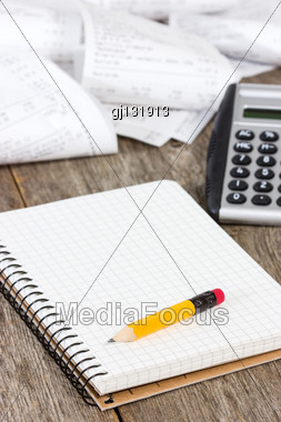 Calculating Expenses. Spiral Notebook, Calculator And Grocery Shopping Receipts Stock Photo