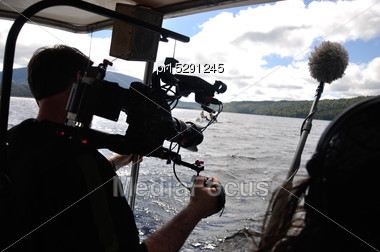 Cameraman And Sound Recordist At Work On The Lake Stock Photo