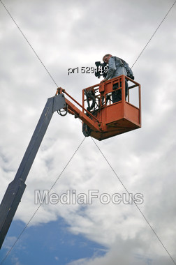 Cameraman Using A Cherry Picker On Location Stock Photo
