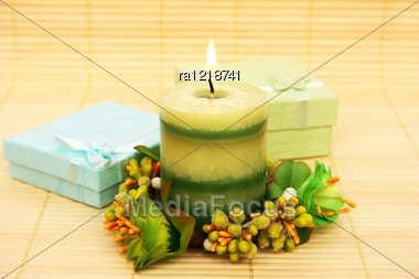 Candle, Flowers And Present Boxes On Bamboo Background. Stock Photo