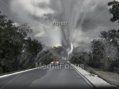 Car Rushes On The Road From Tornado Stock Photo