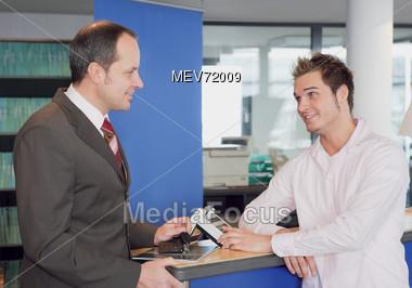 Car Salesman Talking To Customer At Counter Stock Photo