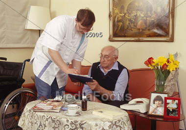 Caretaker Helping Elderly Man Stock Photo
