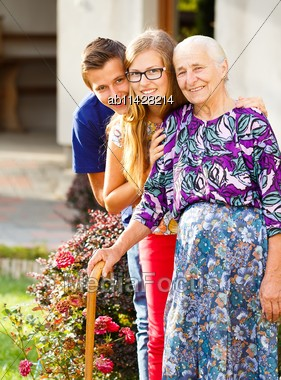 Caring Grandchildren Supporting Their Kind Grandmother With Disabilities Stock Photo