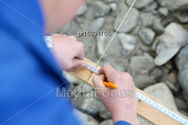 Carpenter Measures The Profile On A Building Site Stock Photo