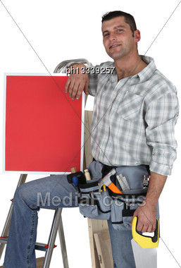 Carpenter With A Red Sign Propped Up On His Knee Stock Photo