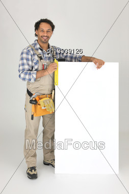 Carpenter With A Try-square And Board Left Blank For Your Message Stock Photo