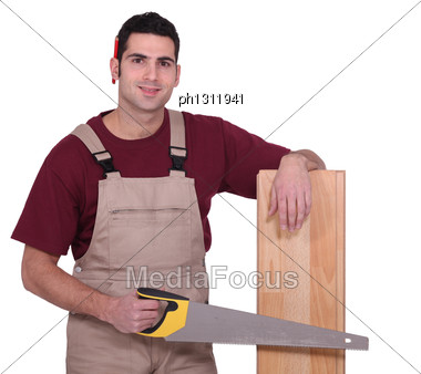 Carpenter With Floorboards And A Handsaw Stock Photo