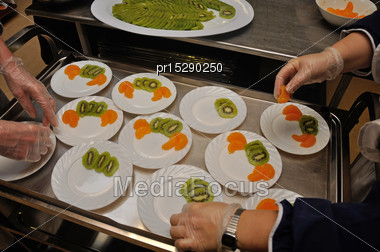 Caterer Prepares Plates Of Dessert With Slices Of Kiwi Fruit And Orange Stock Photo