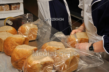 Caterers Bag Up Small Loaves Of Bread For Guests At A Reception Stock Photo