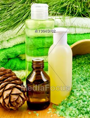 Cedar Oil In A Bottle, Branch Of Cedar Cones, Towels And Salt In A Wooden Bowl, Lotion, Shower Gel On A Wooden Board Stock Photo