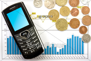 Cell Phone And Coins Over Business Chart Stock Photo