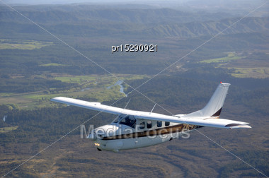 Cessna 210 Light Aircraft Flying Over Bush And Farms In Westland, New Zealand Stock Photo
